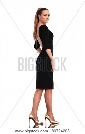 Side view of a gorgeous elegant fashion woman walking on isolated studio background.