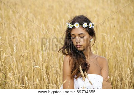 Close up portrait of a beautiful young brunette woman in a wheat field
