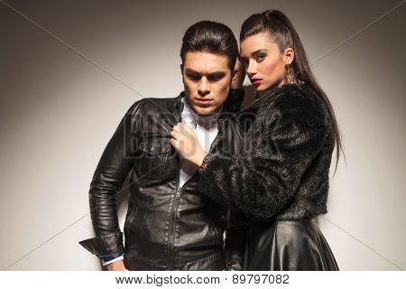 Side view of a gorgeous fashion woman pulling her lovers leather jacket while he is looking down.