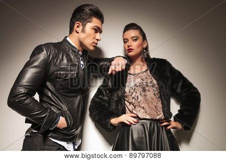 Side view of a handsome fashion man leaning on his girlfriend while holding his hands in pockets.