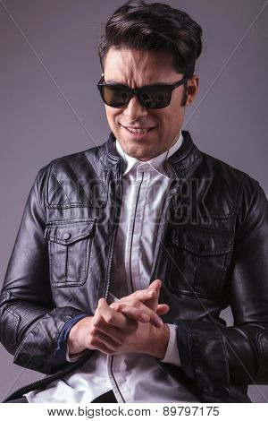 Young fashion man making a funny face while holding his hands together.