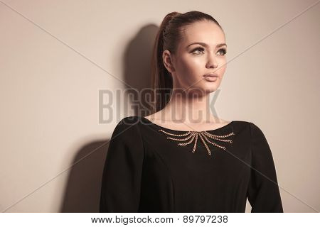 Close up picture of a gorgeous blonde woman posing on grey studio background, looking away from the camera.