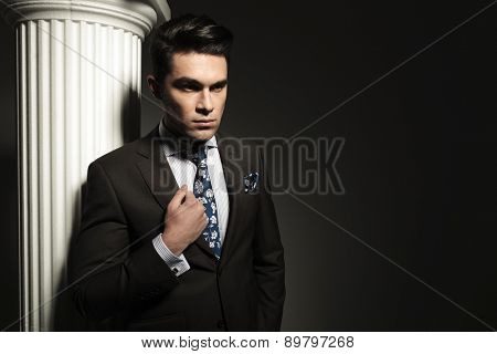 Young business man fixing his collar while looking away from the camera.