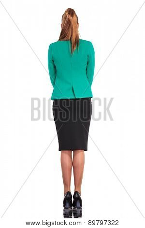 Rear view of a young business woman standing on isoated studio background.