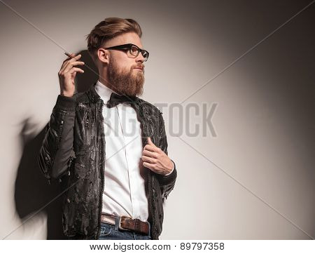 Side view of a hipster young business man looking away from the camera while smoking a cigarette.