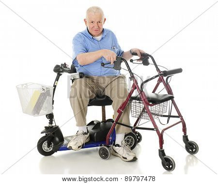 A senior man sitting sideways on his power scooter while holding onto the handles of his wheeling walker.  On a white background.