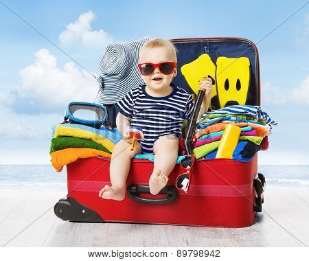 Baby In Travel Suitcase. Kid Inside Luggage Packed For Vacation Full Of Child Clothes