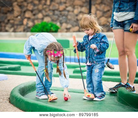 Kids playing golf on a golf course