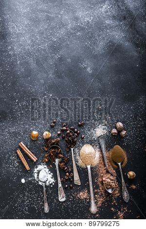 Sweet spices in the spoons on the table a black background