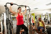 stock photo of pull up  - Determined muscular woman doing pull - JPG