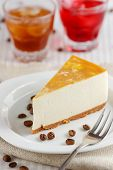 stock photo of cheesecake  - One slice of banana cheesecake on a white plate with two glasses of drinks - JPG