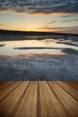 picture of tide  - Beautiful sunrise reflected in low tide water pools on beach landscape with wooden planks floor  - JPG