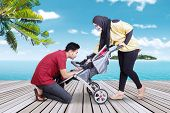 image of jetties  - Portrait of two parents take care their baby in the baby carriage shot on the jetty at tropical beach - JPG