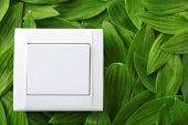 foto of toggle switch  - Light switch on green leaves background - JPG