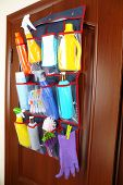 picture of household  - Household chemicals in holder hanging on wooden door background - JPG