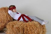 pic of mischief  - Ukrainian girl in national dress and jeans lying in the manger with his hands behind his head - JPG