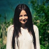picture of young woman posing the camera  - young beautiful woman poses in green thickets looks in the camera - JPG