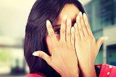 foto of peeking  - Shy woman peeking through covered face - JPG