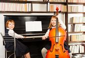 image of cello  - Girls in school uniform dresses playing on the cello and the piano indoors with black and white checked floor - JPG