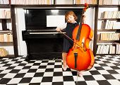 stock photo of cello  - Beautiful small girl in school uniform dress playing on the cello sitting near the piano and shelves with books - JPG