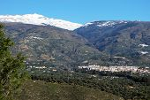 stock photo of snow capped mountains  - View of the town and countryside in the Vale of Lecrin with views towards the snow capped Sierra Nevada mountains Orgiva Vale of Lecrin Las Alpujarras Granada Province Andalusia Spain Western Europe - JPG