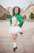 image of wig  - Young woman in irish dance dress and wig dancing outdoor - JPG