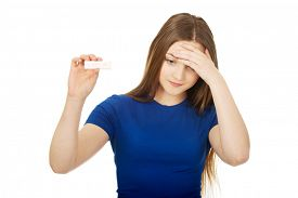 image of teen pregnancy  - Unhappy teenage woman holding pregnancy test - JPG