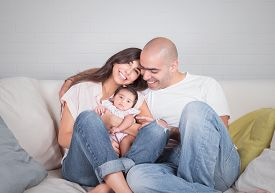 stock photo of couch  - Portrait of happy cheerful family sitting on the couch at home - JPG