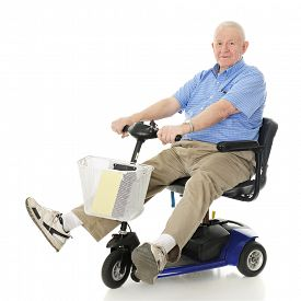 stock photo of crippled  - A senior man delightedly driving his electric scooter - JPG