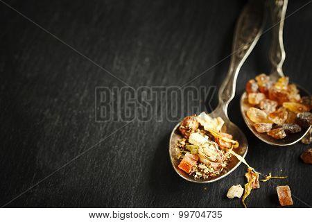 Rooibos Tropica Herbal Tea And Brown Sugar In Spoons On Black Background
