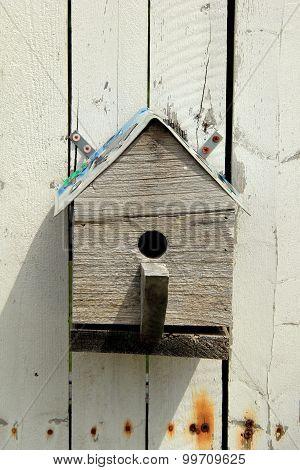 Little wood birdhouse on white board