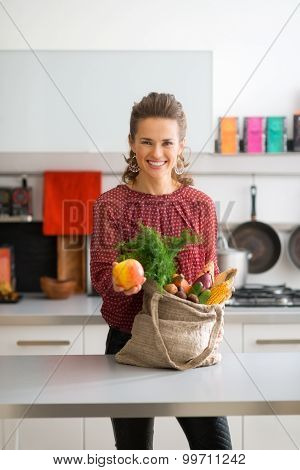 Happy Woman With Bag Of Fresh Produce Holding Out An Apple