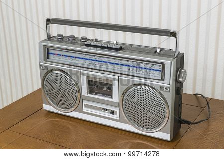 Old boom box radio cassette recorder on wood table.