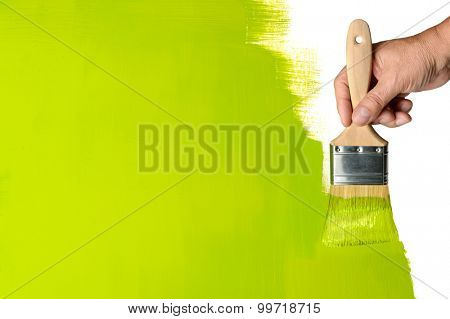 Man's hand using paintbrush with green Paint on wall