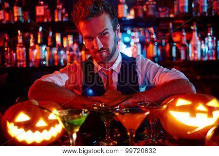 Bartender of Halloween night looking at pumpkin