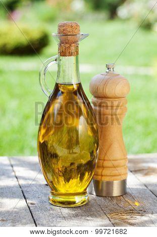 Olive oil bottle and pepper shaker on wooden table