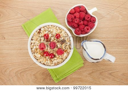 Healty breakfast with muesli, berries and milk on wooden table