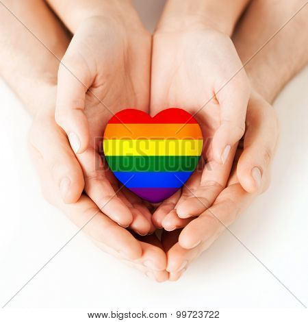 gay pride, homosexual, love and charity concept - close up of male and female hands holding small rainbow heart