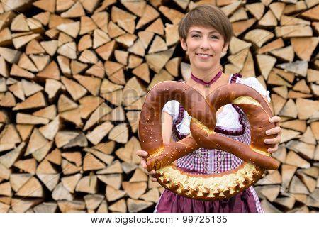 Smiling Bavarian Woman Holding A Large Pretzel