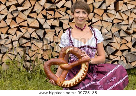 Young Woman In A Dirndl Holding A Large Pretzel