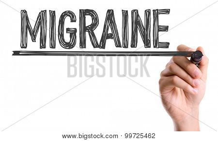 Hand with marker writing the word Migraine