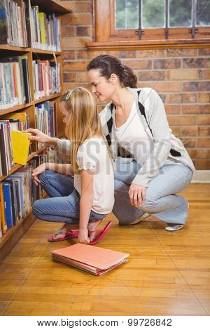 Teacher helping a student pick a book at the elementary school