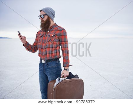 lone hipster with awesome beard using smart phone in desolate salt flats holding retro suitcase with copyspace composition