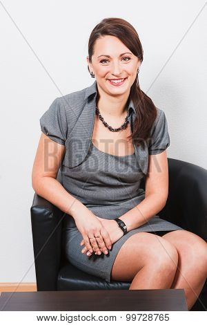 Smiling woman resting on arm-chair