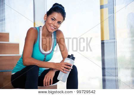 Happy sports woman resting on the stairs in gym with bottle of water