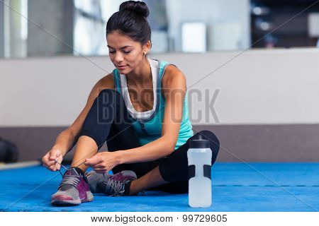 Sports woman tie shoelaces in gym
