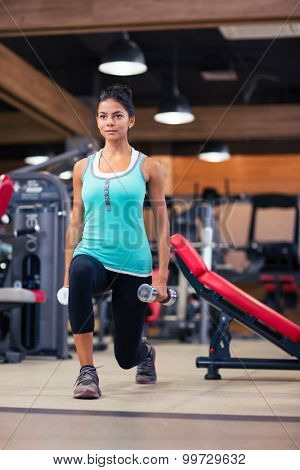 Full length portrait of attractive woman workout with dumbbells in fitness gym