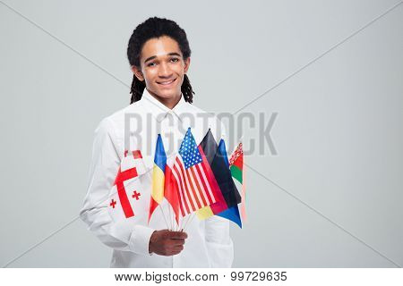 Portrait of a happy afro american businessman holding world flags over gray background