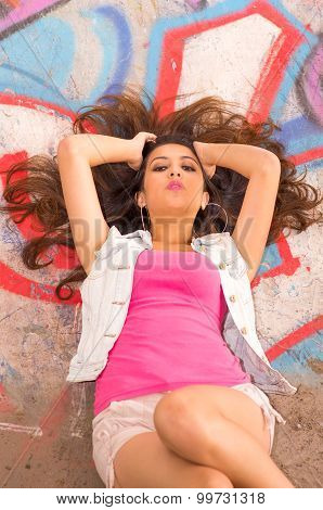 Brunette model wearing pink top, white vest and wild hairstyle lying down on concrete skatepark surf
