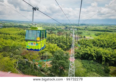 NATIONAL COFFEE PARK, COLOMBIA, Downward view of green cable car descending by, inside National Coff